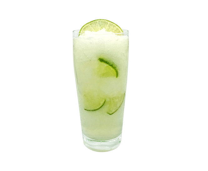 Frozen margarita recipe in a tall glass with limes.